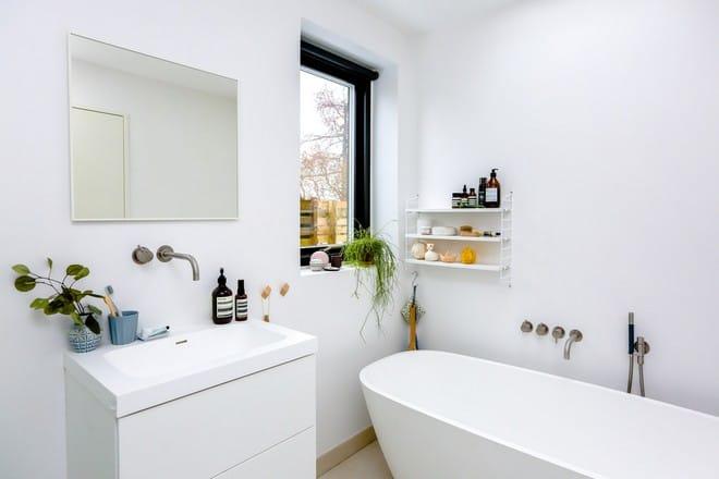 Witte badkamer met ligbad en witte wastafel